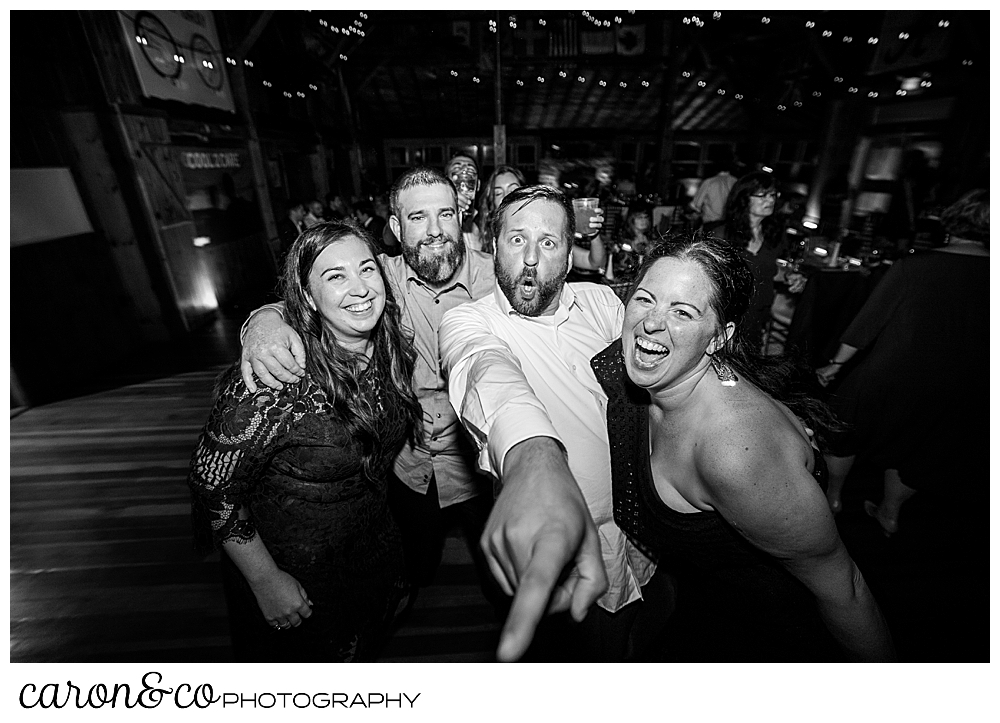 black and white photo of two men and two women dancing, facing the camera, one man is pointing at the photographer