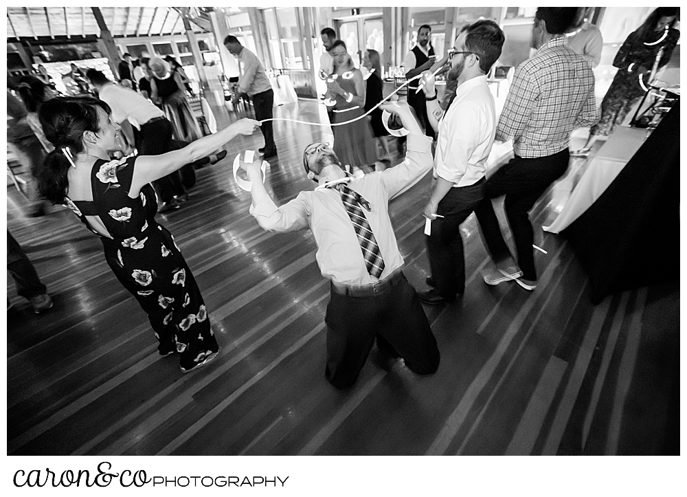 black and white photo of a groom doing the limbo