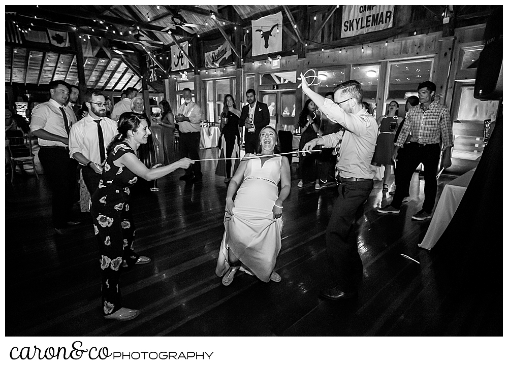 black and white photo of a bride doing the limbo