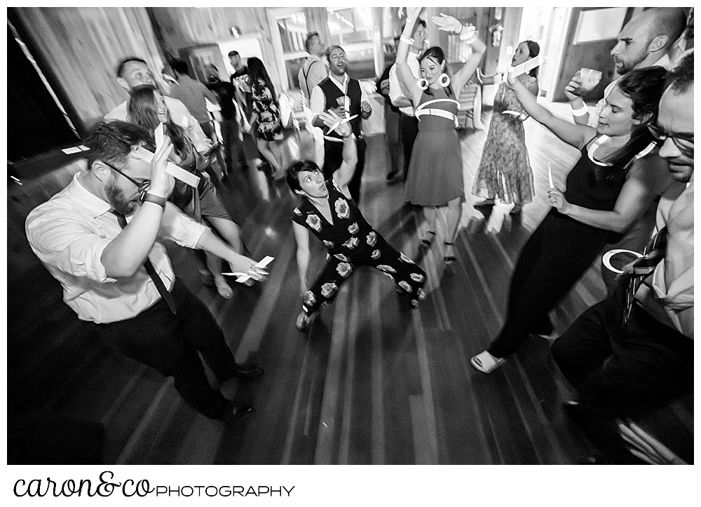 black and white photo of a woman dancing at a camp skylemar wedding reception, there are wedding guests dancing around her
