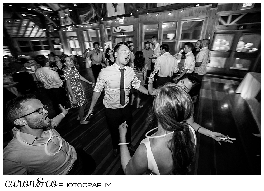 black and white photo of a wedding guest in the middle of the dance floor, singing and dancing