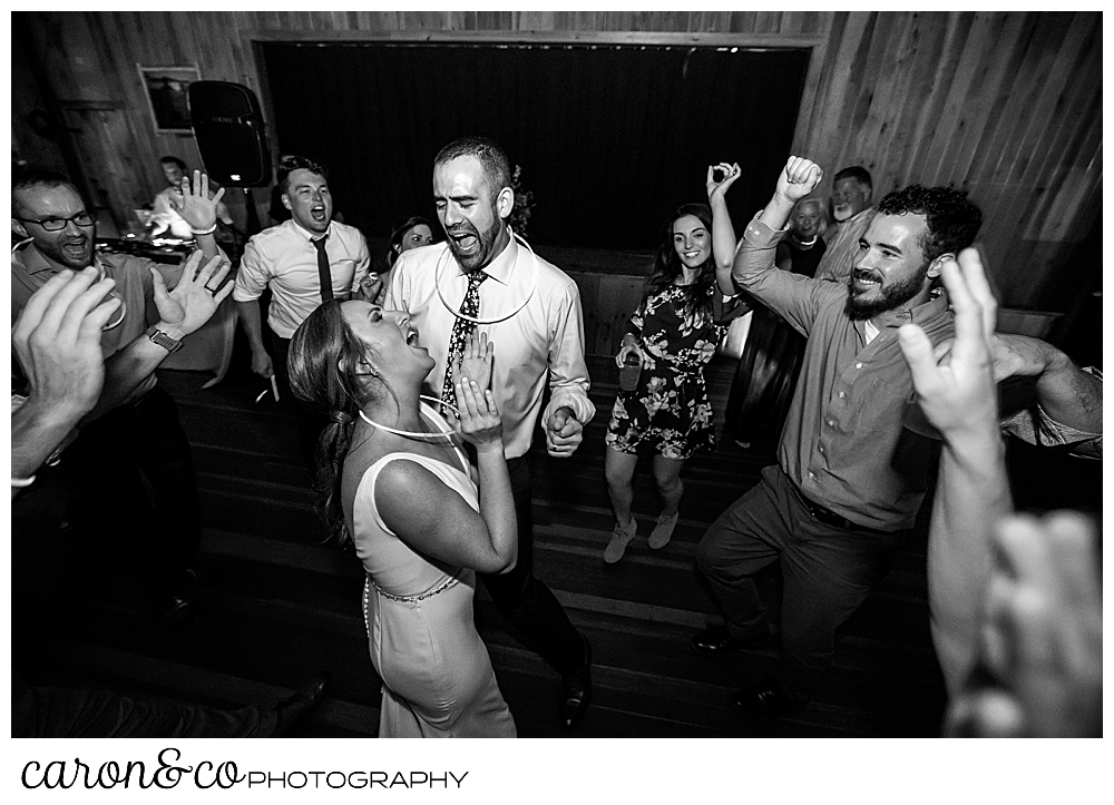 black and white photo of a bride and groom dancing and singing among their guests at their Camp Skylemar wedding reception