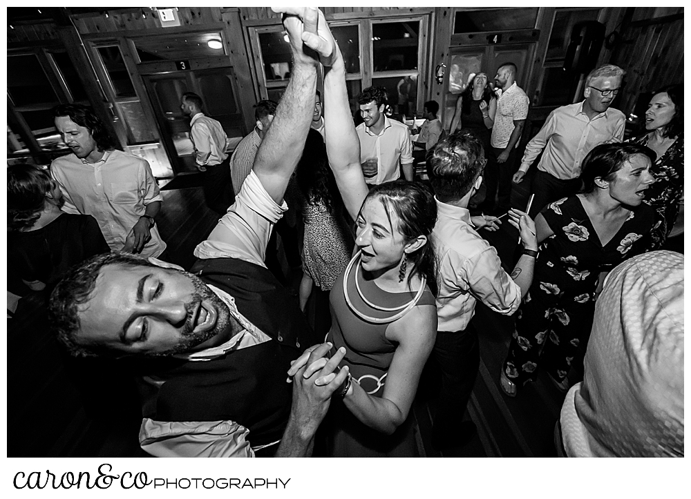black and white photo of wedding guests dancing at a Camp Skylemar wedding reception