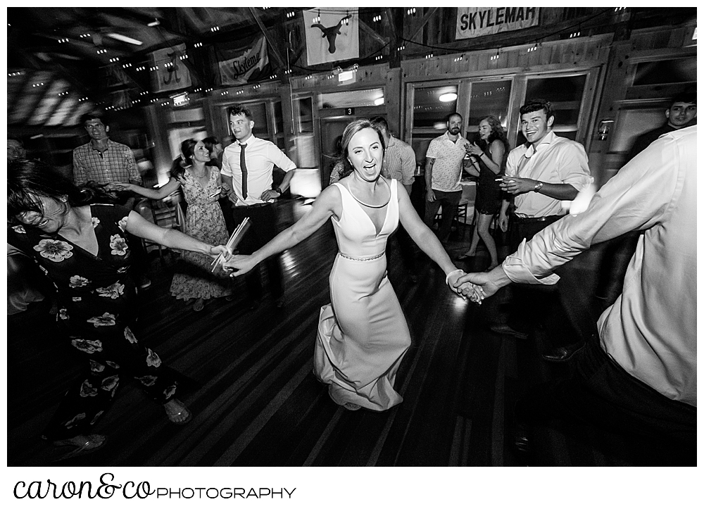 black and white photo of a bride holding hands with her wedding guests, and dancing and singing