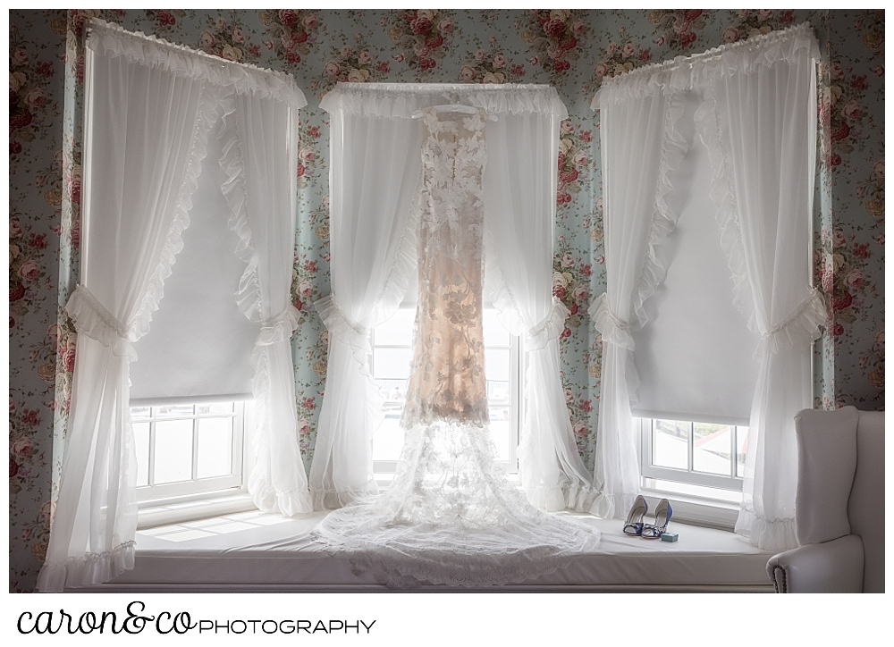 a blush wedding dress hanging in a flowered wallpapered room