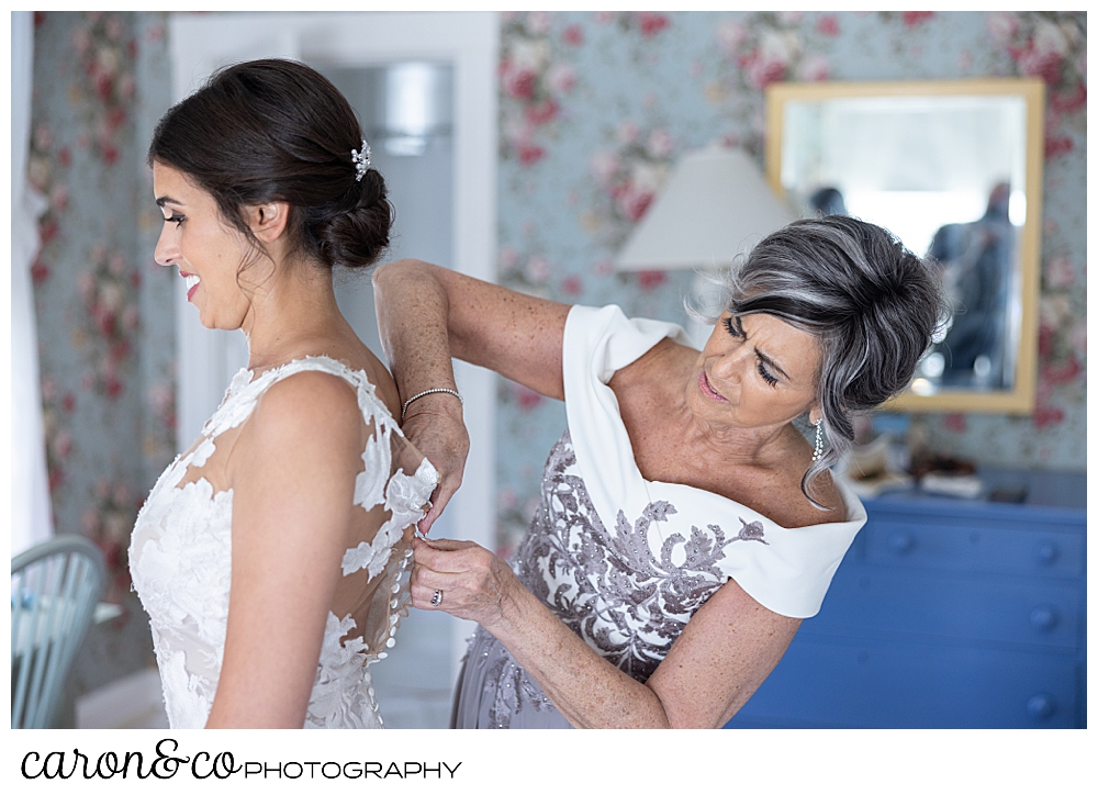a mother helps her daughter fasten the back of her wedding dress at a coastal maine wedding at the colony hotel Kennebunkport maine