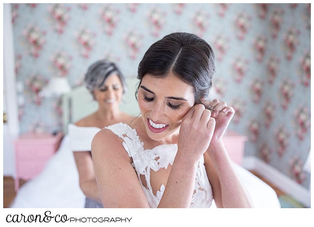 a dark haired bride, puts on an earring
