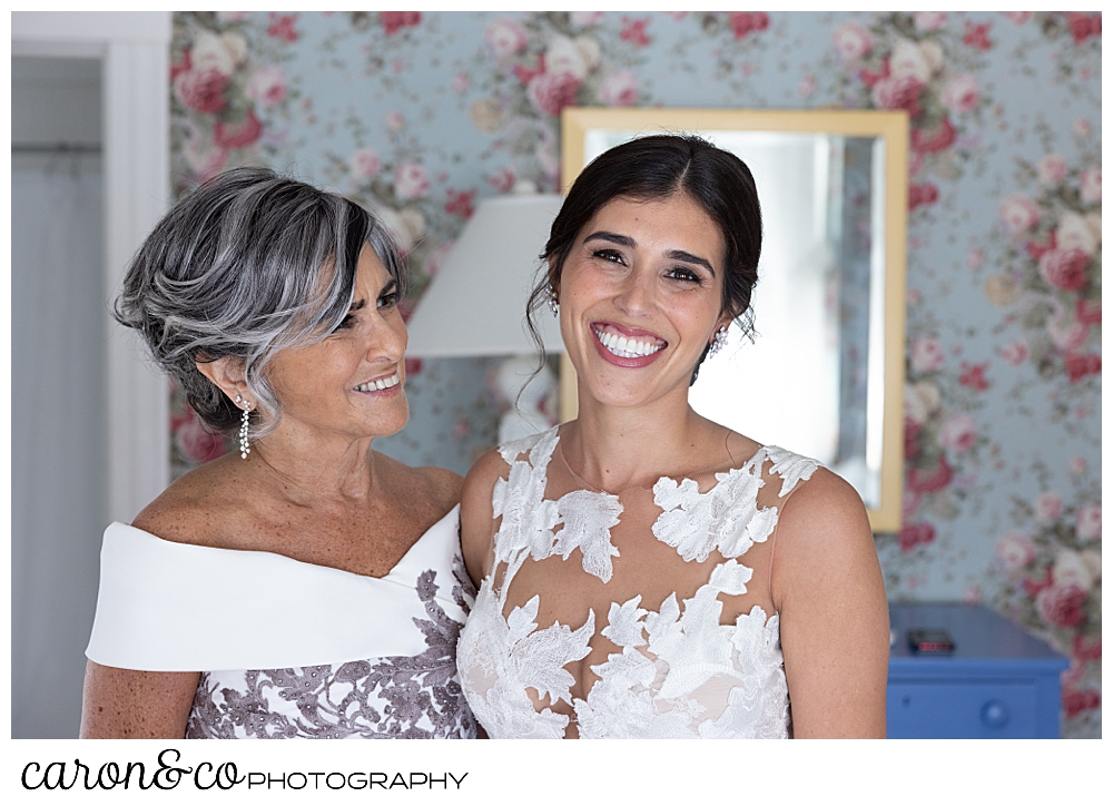 a bride and her mother stand together, the bride's mother is looking at the bride, and the bride is looking at the camera