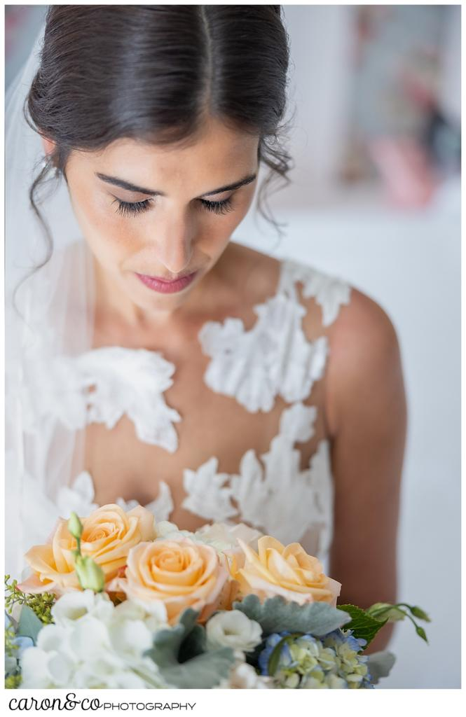 a bridal portrait of a dark haired bride, looking down at her pink, white and green bridal bouquet