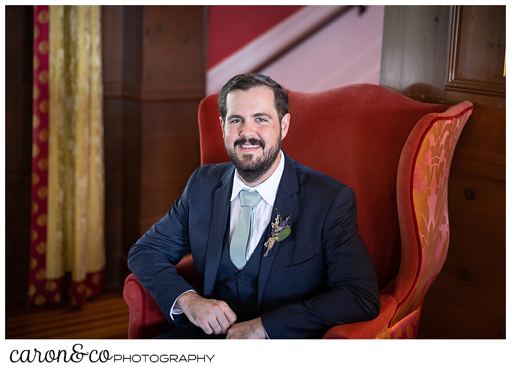 a groom portrait, of a dark haired, bearded groom sitting in a red chair
