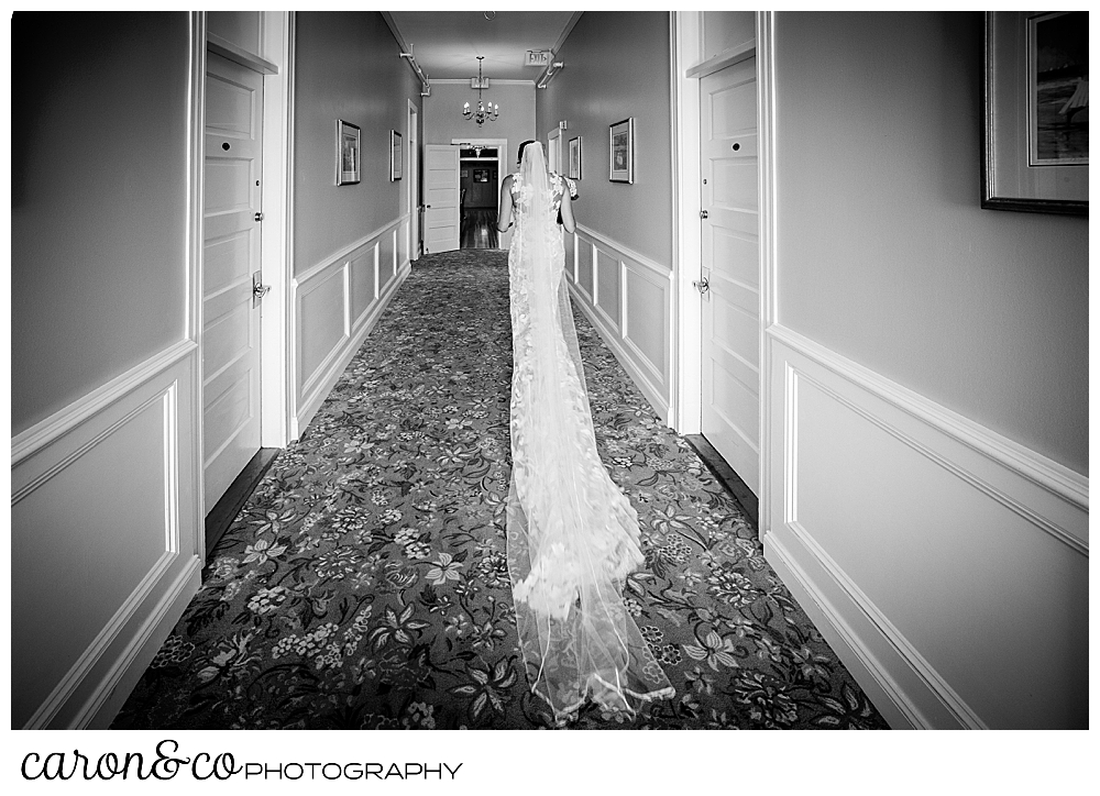 black and white photo of a bride walking down a hallway, away from the camera