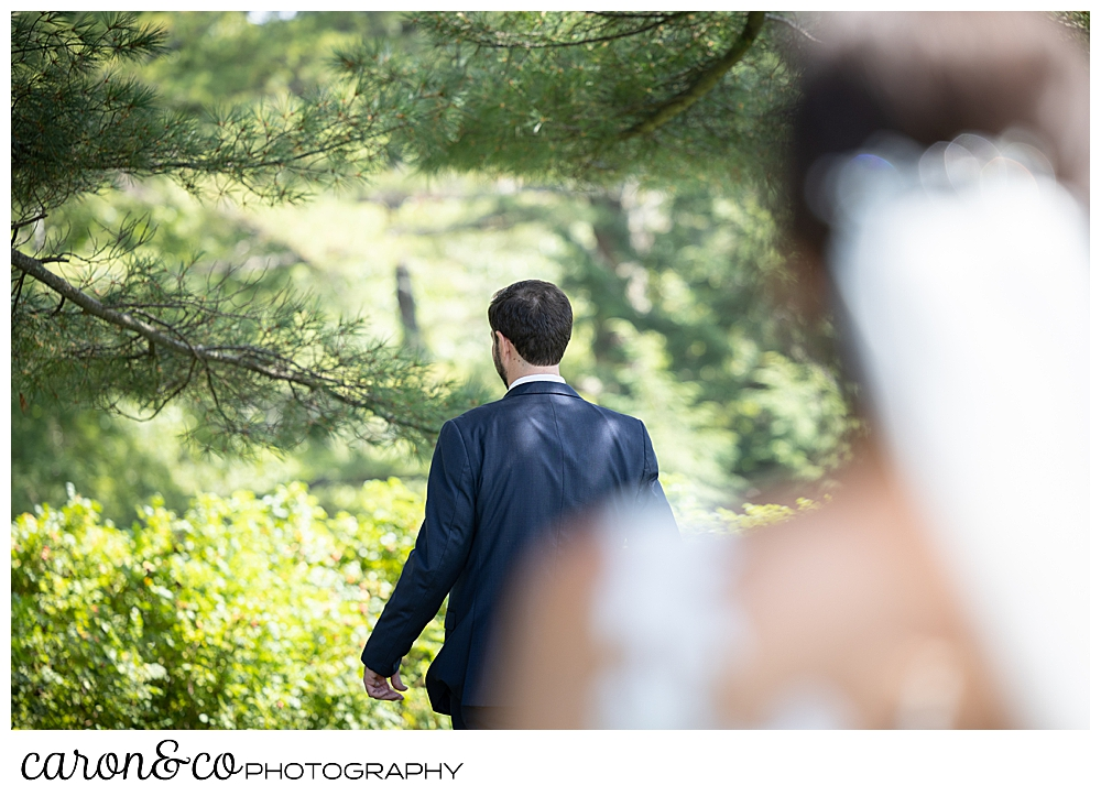 in the foreground is a dark-haired bride wearing a white veil, a groom with his back turned in the background at a Maine wedding day first look at the Colony Hotel Kennebunkport Maine