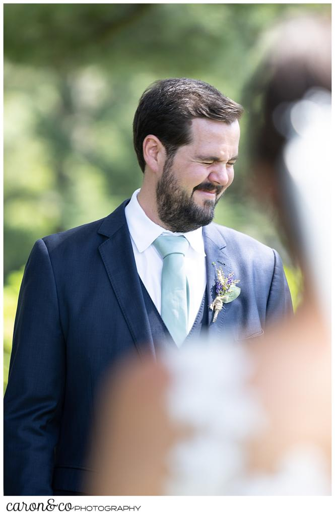 a groom, shuts his eyes tight as he approaches his bride during a Maine wedding day first look at the Colony Hotel, Kennebunkport, Maine