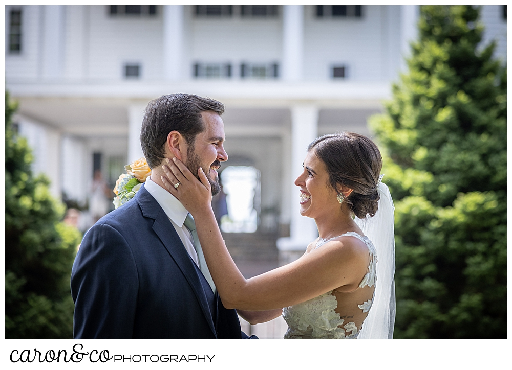 a dark-haired bride holds the face of her dark-haired groom during a Maine wedding day first look at the Colony Hotel Kennebunkport Maine