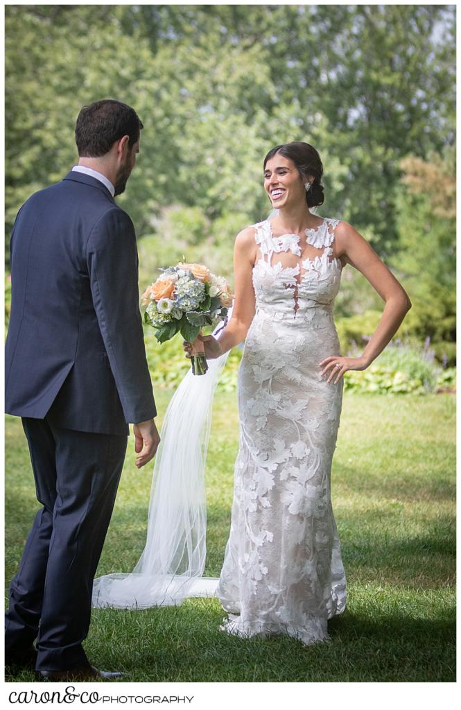a dark-haired bride, holding a pink, white, blue, and green bouquet, stands before her groom, her hand is on her hip