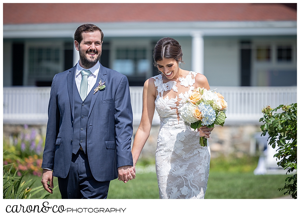 a bride and groom walking on the lawn of the Colony Hotel, the bride is looking down while she holds a bouquet of white, pink, blue, and green
