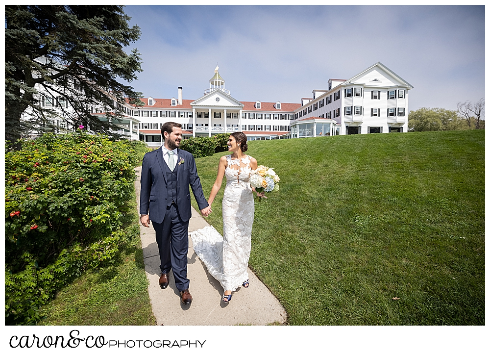 a dark-haired bride and groom walk on the walkway in front of the Colony Hotel, Kennebunkport, Maine
