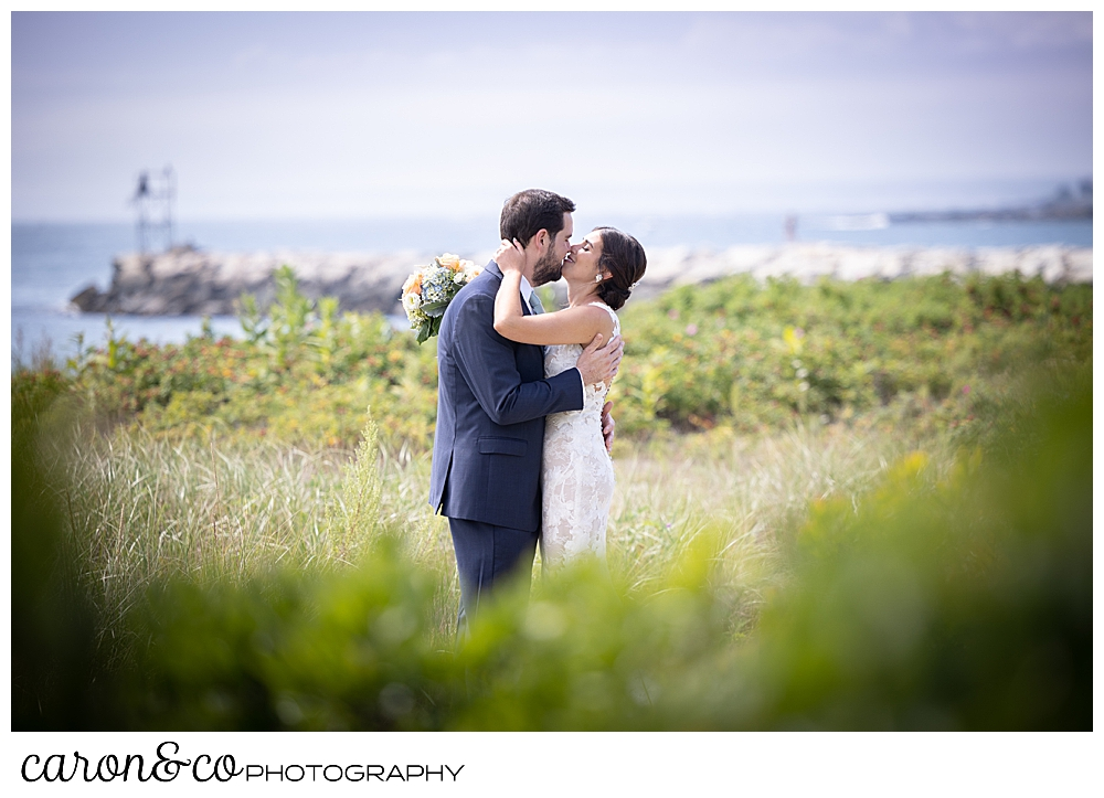 a dark-haired bride and groom kiss in the dunes at Colony Beach, Kennebunkport, Maine
