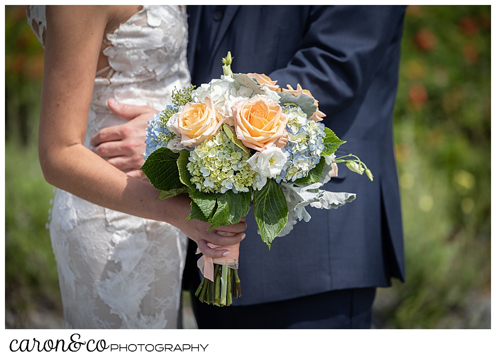 in the background is a bride and groom embracing, in the foreground is the bride's bouquet of pink, white, blue, and green