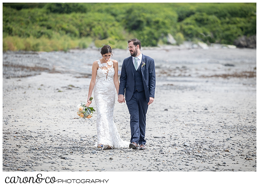 a dark-haired bride and groom hold hands and walk on Colony Beach in Kennebunkport, Maine