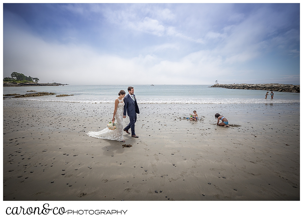 a bride and groom walk on Colony Beach in Kennebunkport, Maine, while children play in the sand