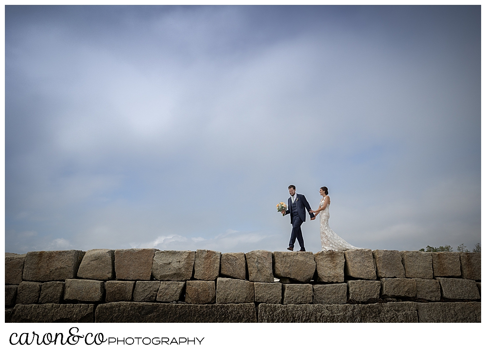 a bride and groom walk on the top of the Kennebunkport Breakwater, the groom is holding the bride's bouquet