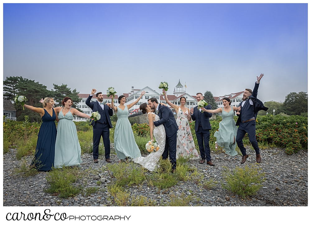 a bride and groom kiss amid their bridal party who is cheering, the colony hotel is in the background