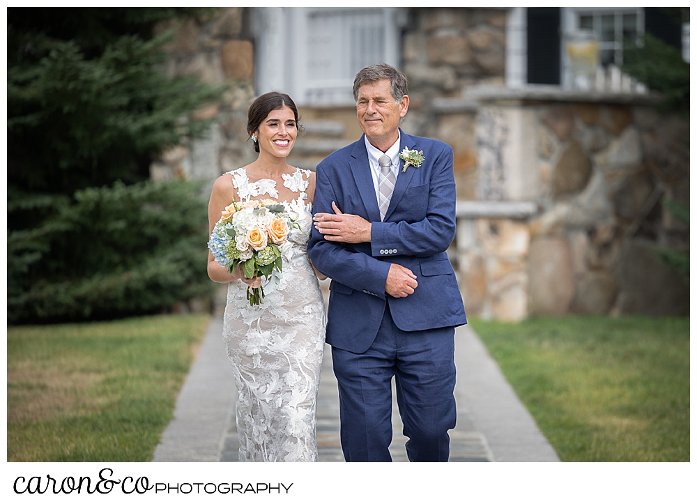 a bride and her father walk down the aisle at an outdoor wedding ceremony at the Colony Hotel, Kennebunkport, Maine