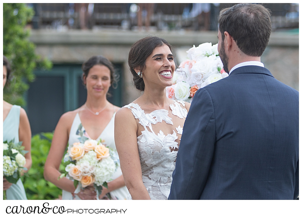 a bride smiles at her groom during an outdoor coastal maine wedding at the colony hotel Kennebunkport maine