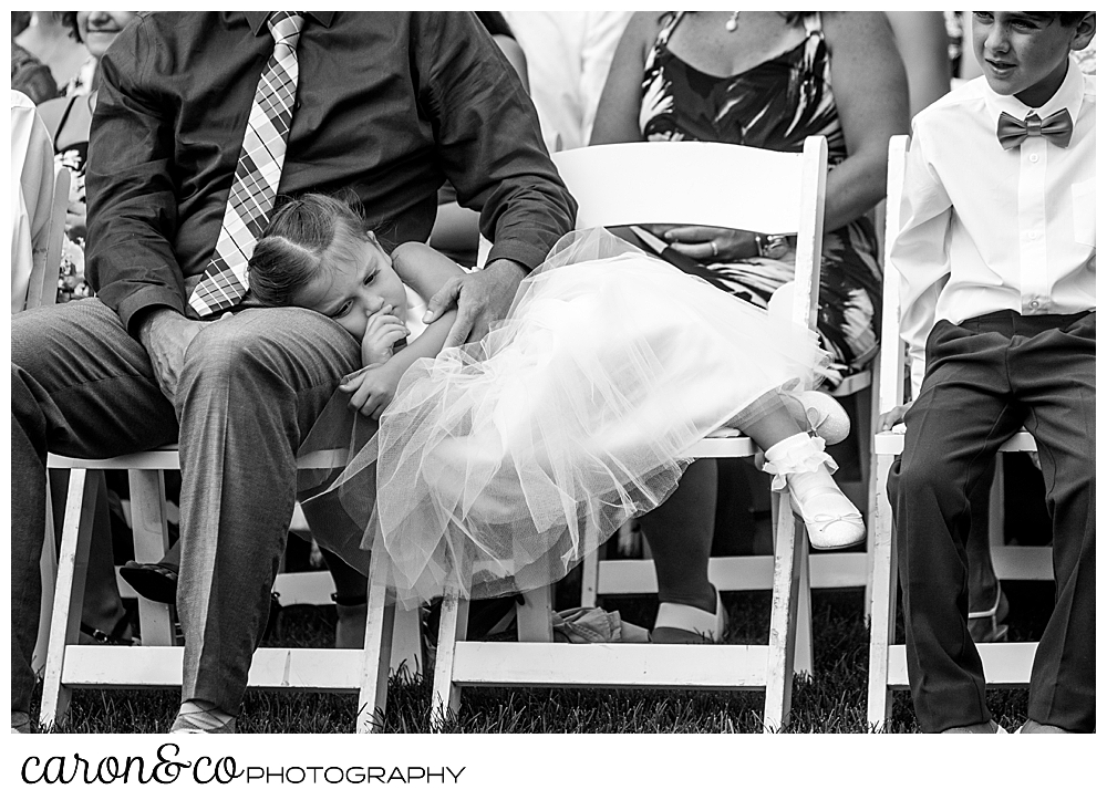 black and white photo of a flower girl resting in her chair, her head in her father's lap