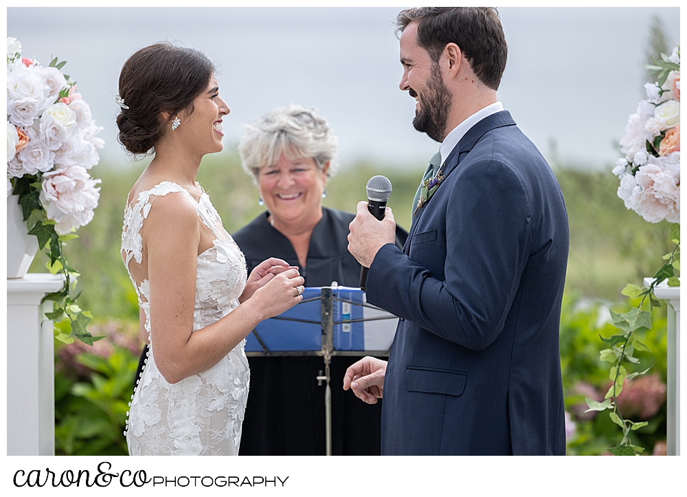 a bride and groom stand before their officiant, the groom has a microphone and is speaking his vows