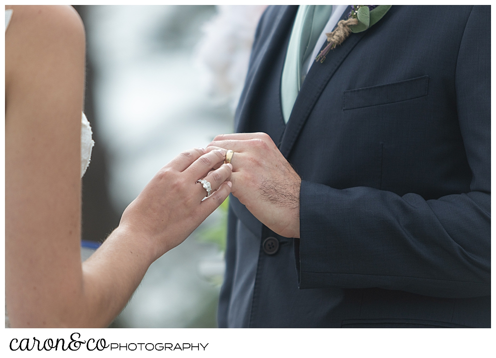 a bride's hand is putting a wedding band on a groom's hand