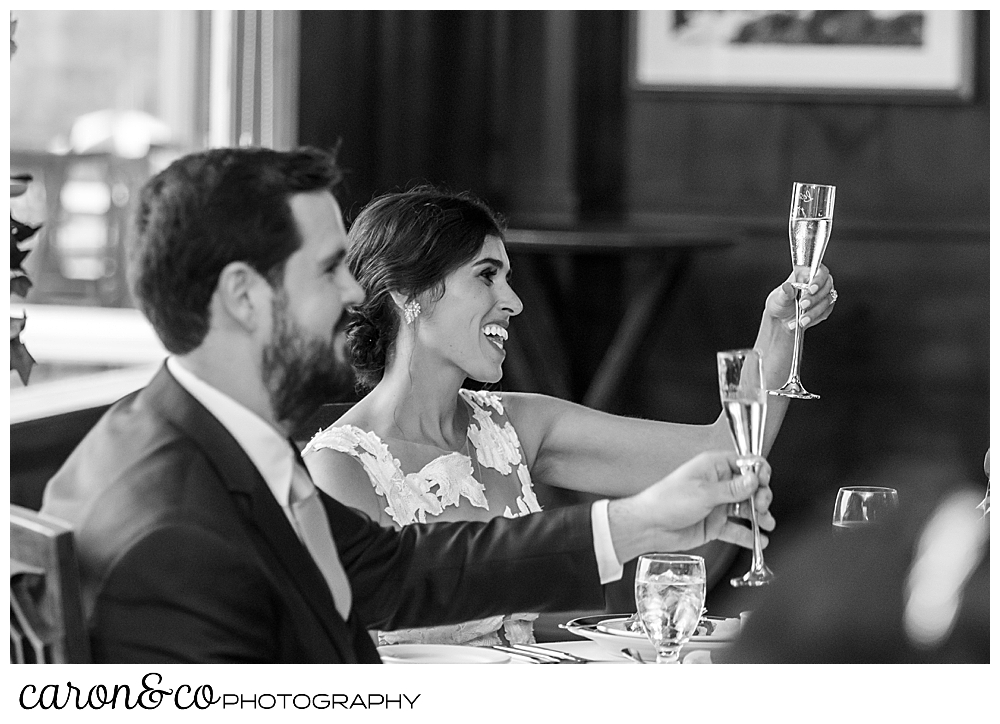 black and white photo of a bride and groom lifting their champagne glasses for a toast