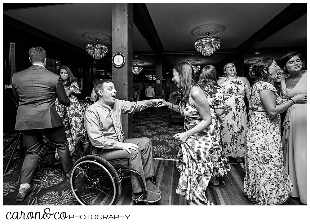 black and white photo of a man in a wheelchair and woman dancing at a wedding at the Colony Hotel