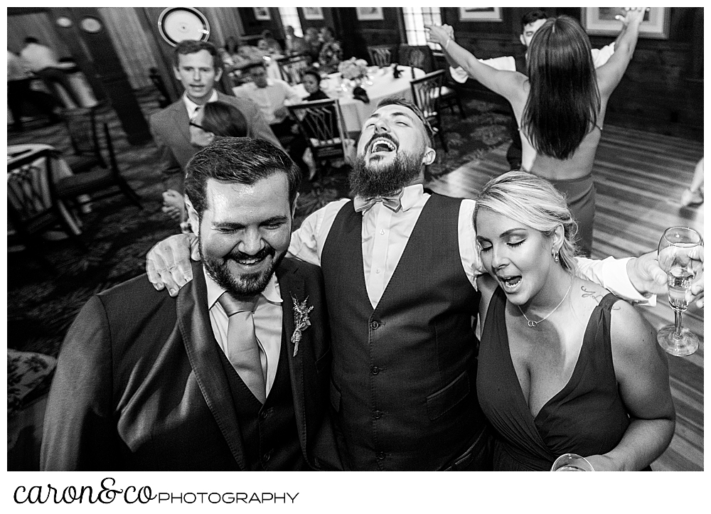 black and white photo of a groom dancing with wedding guests