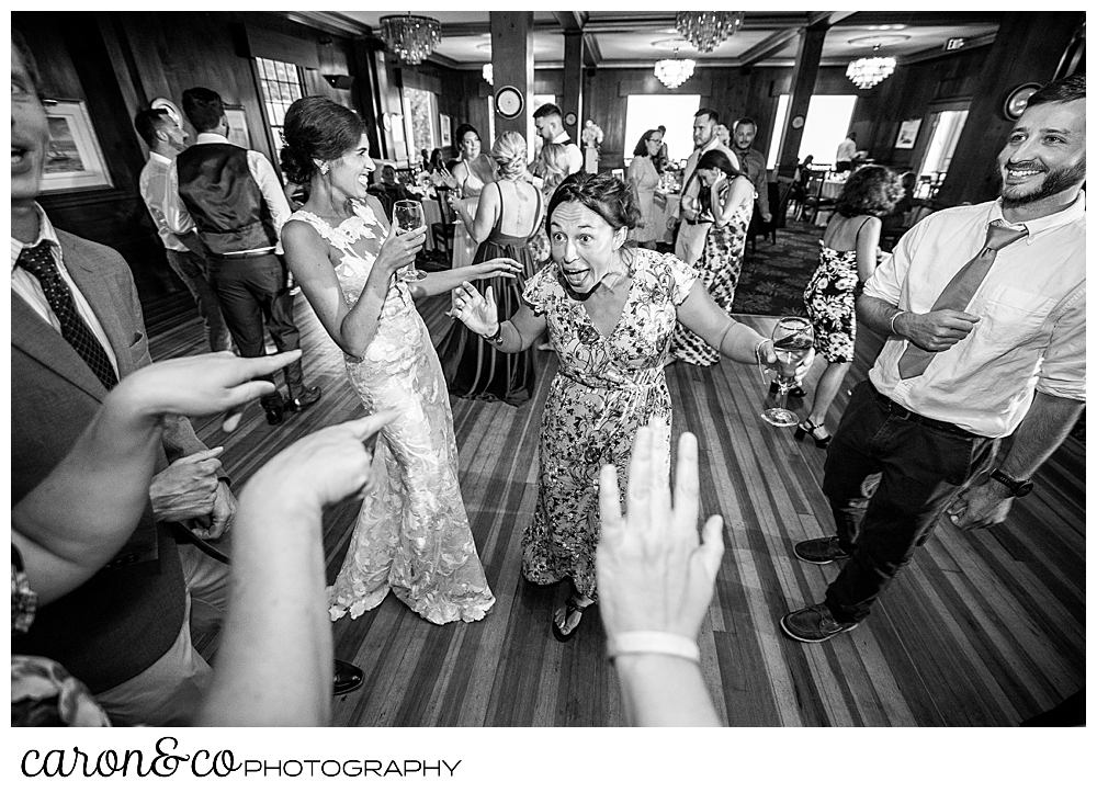 a black and white photo of a bride dancing with a friend, hands in the foreground are pointing to the women