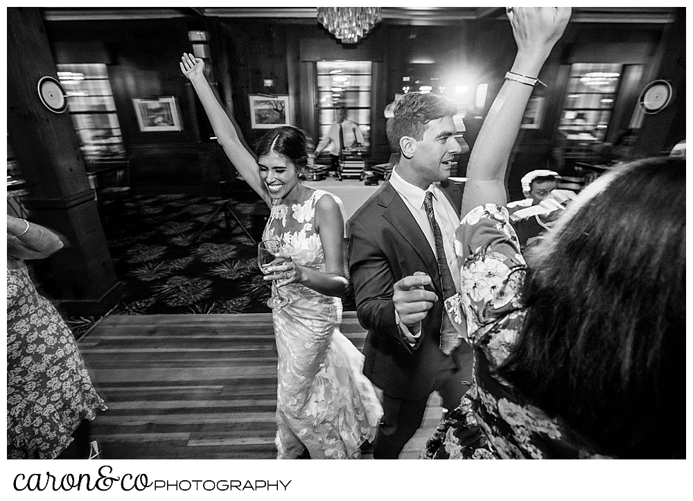 a bride on the dance floor with wedding guests, her arm is raised above her head