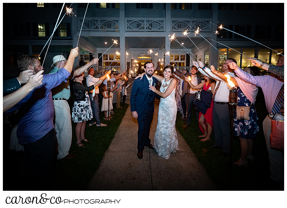 a bride and groom walk through a sparkler exit on coastal Maine wedding at the Colony Hotel Kennebunkport Maine