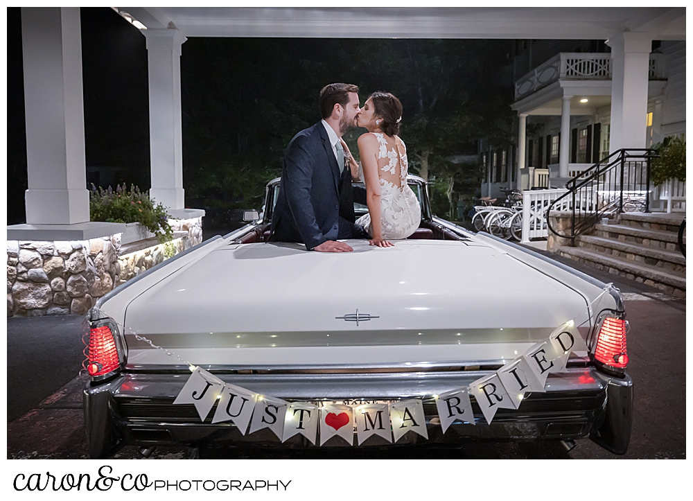 a bride and groom sitting on the back of a vintage white Lincoln Continental convertible with the top down, they are kissing, and the sign on the bumper reads just married, at the steps of the Colony Hotel Kennebunkport Maine