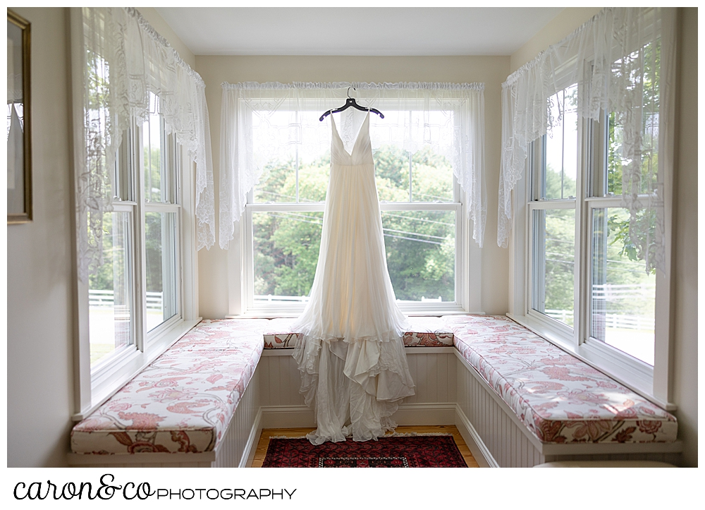 a wedding dress hangs in a alcove of windows