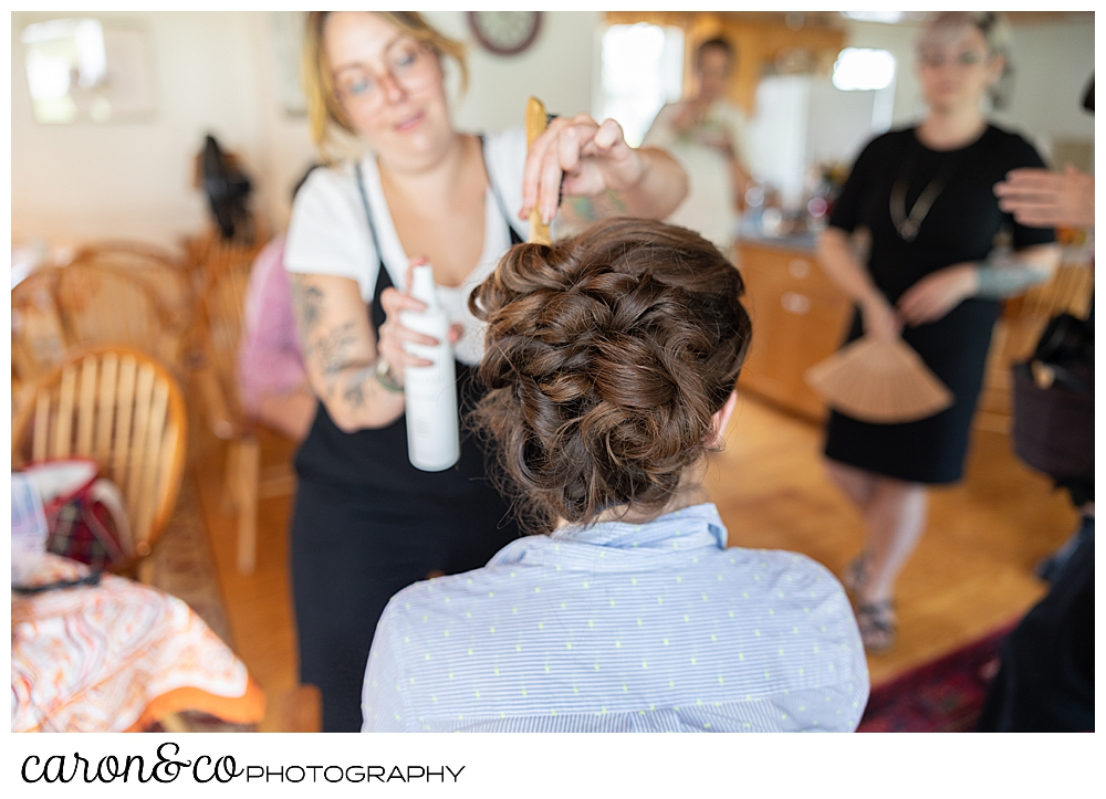 a bride having an updo done, gets sprayed with hairspray