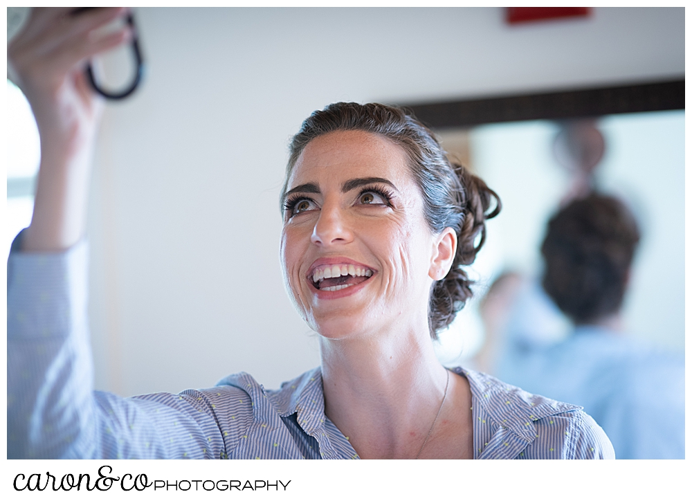 a bride checks her hair in a mirror behind her, and smiles