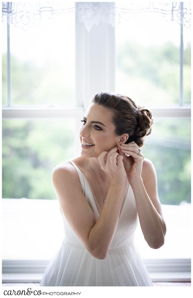 a bride, seated in a window seat, puts on an earring