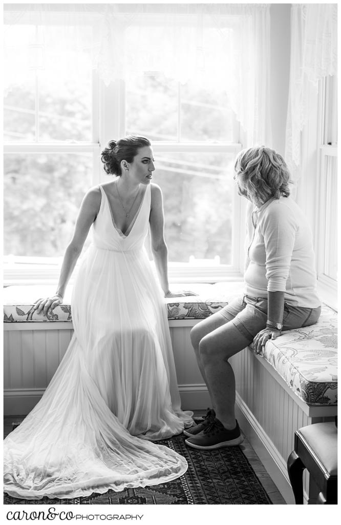 black and white photo of a bride in a sleeveless white dress, and her mother sitting on window seats