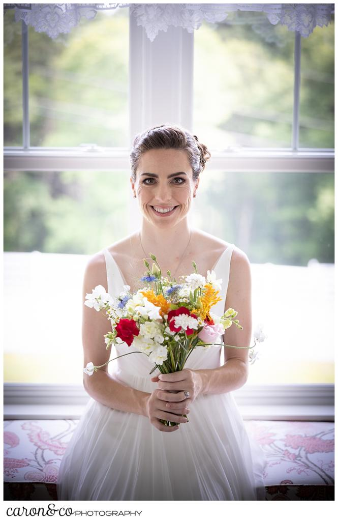 a smiling bride seated on a window seat, holding a bright colored bouquet of wildflowers
