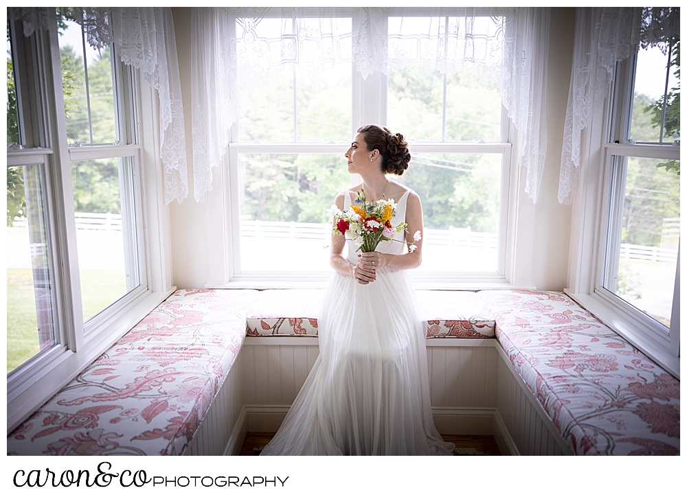 a bride sits on an alcove window seat, holding a bright colored wildflower bouquet, her head is turned as she looks out a window