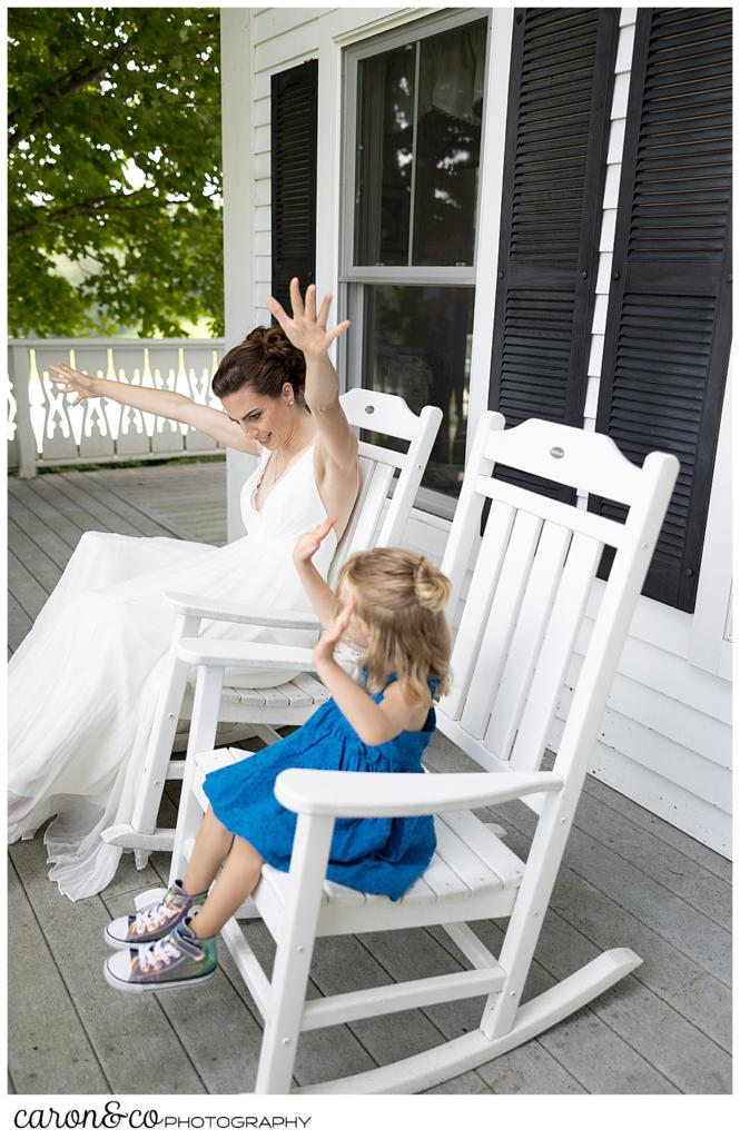 a bride, wearing a sleeveless white dress, sits on a porch in a white rocking chair, next to a small girl wearing a turquoise dress, they have their hands up in the air