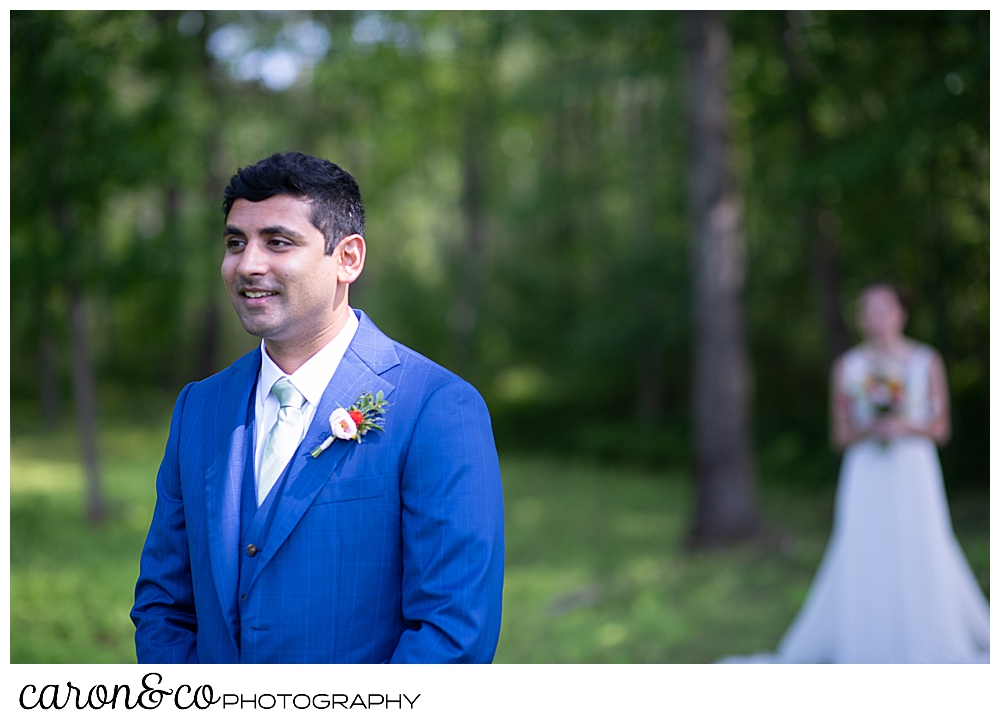 a groom in a blue suit stands with his back to his bride, seconds before their Maine wedding day first look