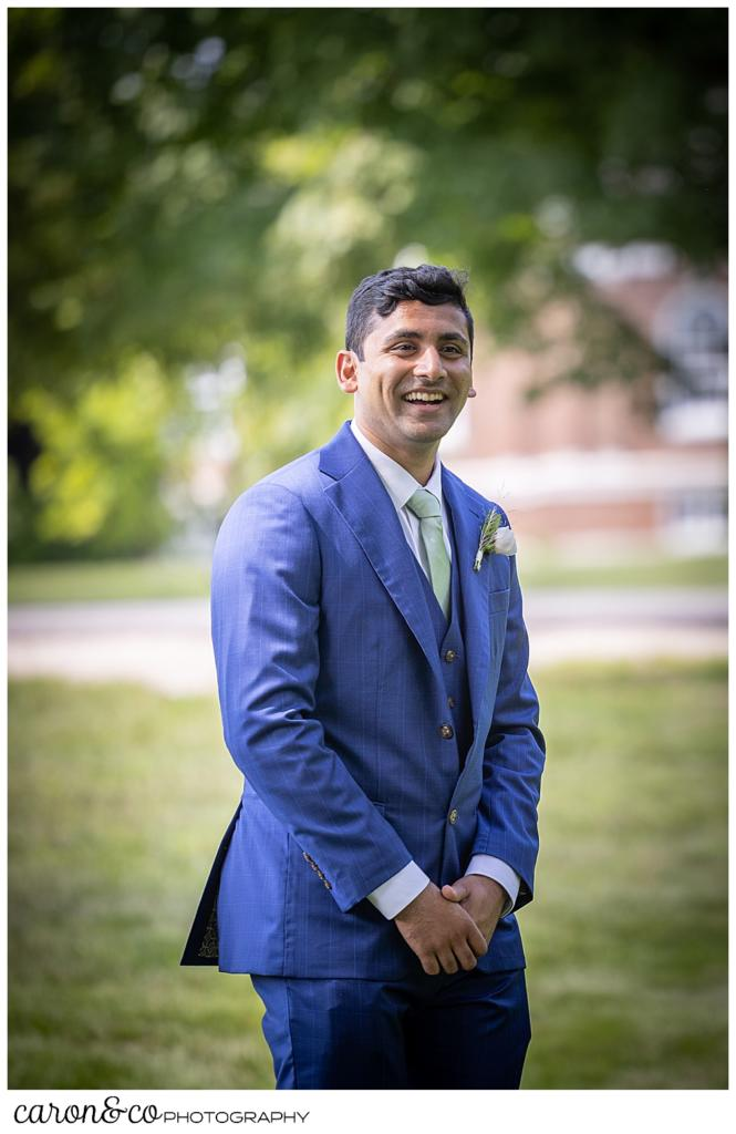 a groom in a blue suit, turns to see his bride during their Maine wedding day first look