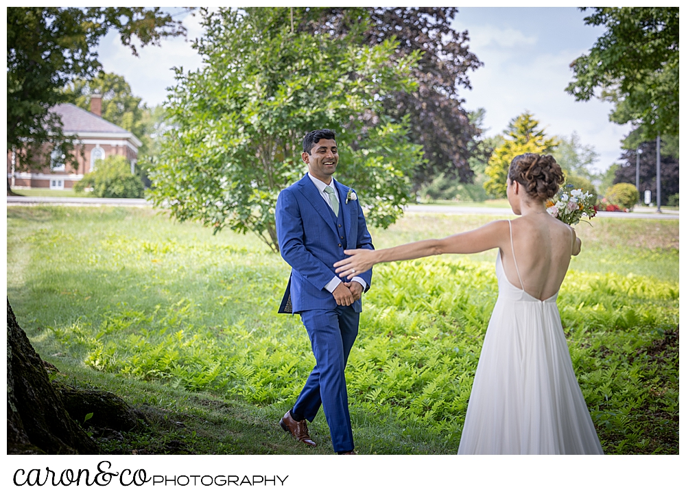a bride in a sleeveless white dress holds her arms out to her groom wearing a blue suit, who is approaching her during their Maine wedding day first look